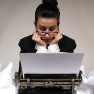 perplexed woman sitting at a typewriter